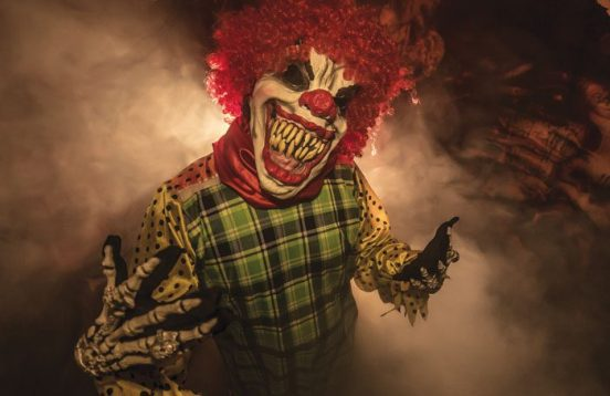 sharp-toothed clown from haunted house, surrounded by fog and dramatic lighting