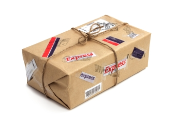 mail package, wrapped in craft paper and tied with twine; express stickers and stamps cover every surface