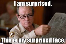 Tommy Lee Jones peering around a paper; meme reads: I am surprised. This is my surprised face. (he is not surprised)