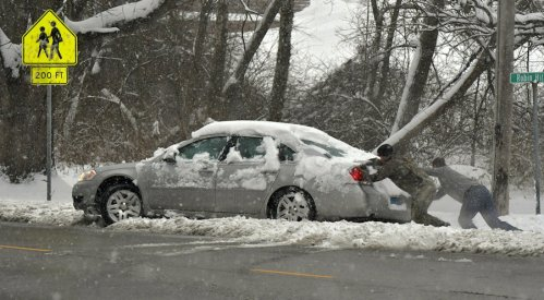 two people pushing a car off side of the road in the snow