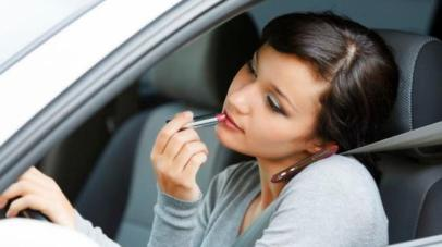 woman applying lipstick and talking on the phone while driving