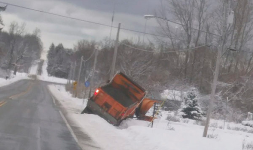 snow plow tipped off side of road in light snow