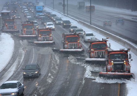snow plows clearing highway; six in a diagonal, working efficiently